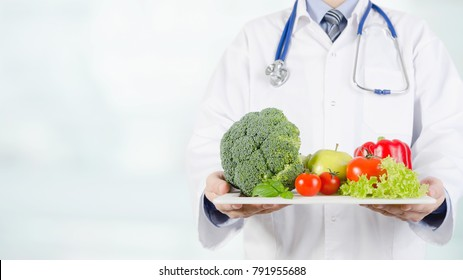 Doctor holding vegetables and fruits on a tray. Diet, nutrition, health care concept. Web banner background with copy-space