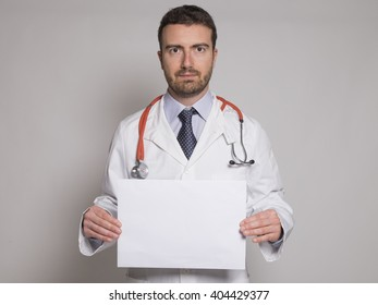 doctor holding a white copyspace billboard isolated on gray background
