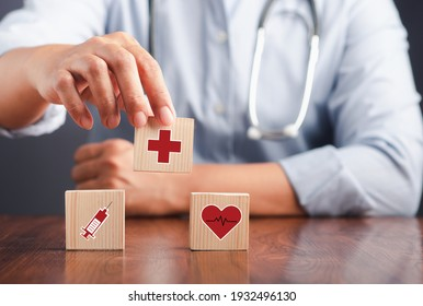 A doctor holding wooden dice with icons of health and doctors in his hands. Close-up photo. Space for text. Concept of doctor work in maintaining human health
