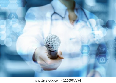 Doctor holds out the microphone on blurred background.