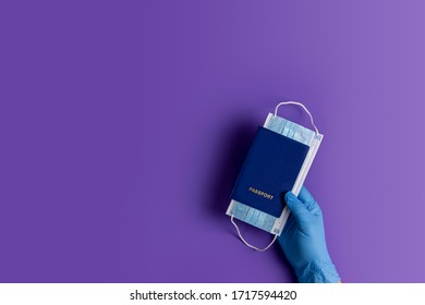 Doctor holds passports and respiratory surgical face mask in hands blue medical glove on violet background. Pandemic corona virus, insurance, airborne diseases, SARS, grippe