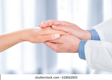The doctor holds the patient's hands. He gives him hope and supports him.