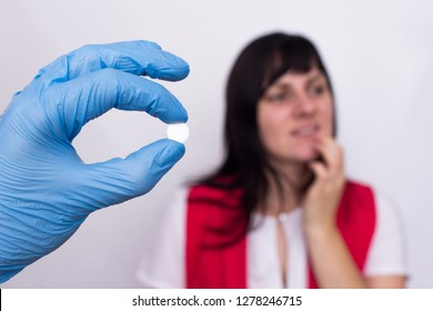 Doctor holds a pill in her hand from oral herpes, the girl holds her lip, pills against herpes, medic