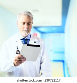 Doctor in the hospital hallway looking at tablet