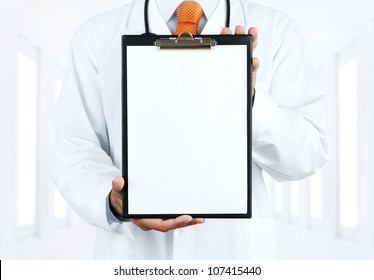 Doctor at hospital holding blank clipboard with copy space