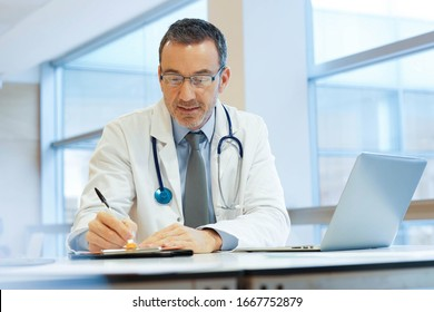 Doctor in hospital office working on laptop