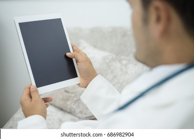Doctor in hospital using a digital tablet while take a rest.