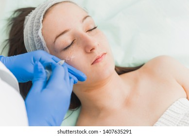 Doctor injecting hyaluronic filler in cheek of young female patient, Corrective medicine concept