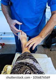 A doctor is injecting local anesthetic in the patients foot in preparation for surgery of a tailor's bunion.