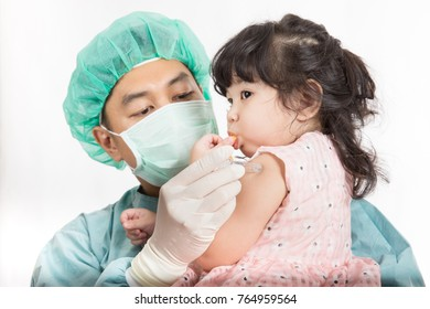 Doctor injecting vaccination in arm of Asian cute little girl in clinic,Vaccination, healthy and medical concept