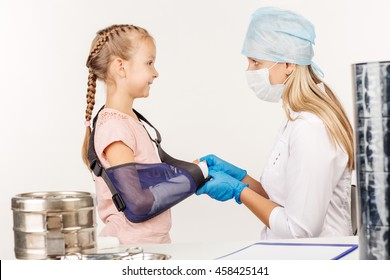 doctor inspecting broken hand of little patient. medicine, health care and people concept