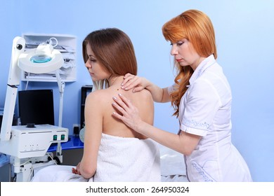Doctor inspecting woman patient skin on her for melanoma