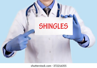 Doctor keeps a card with the name of the diagnosis -?? shingles. Selective focus. Medical concept.