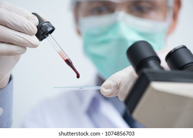 Doctor or lab technician dripping human red blood on slide glass for malaria test (thick film), blood group test, complete blood count (CBC) with microscope in hospital laboratory. close up