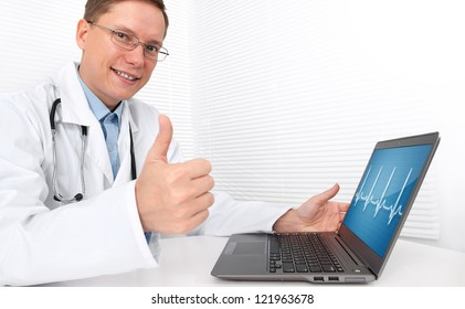 Doctor with laptop sitting in doctor's office and showing his thumb up