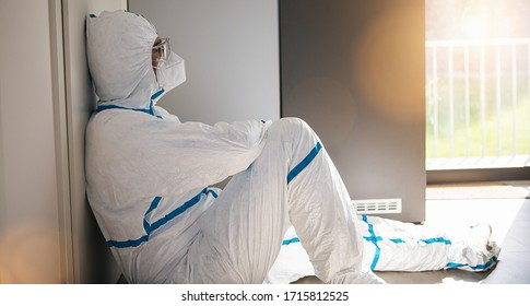 Doctor lies in protective clothing with stress and burnout in clinic leaning against window at Covid-19 coronavirus epidemic