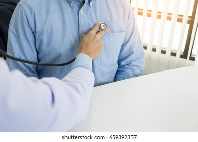 Doctor listening to cheerful young patients chest with stethoscope in his office at the hospital