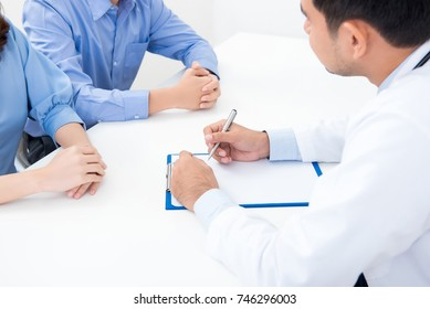 Doctor listening and taking note while consulting with couple patients in hospital
