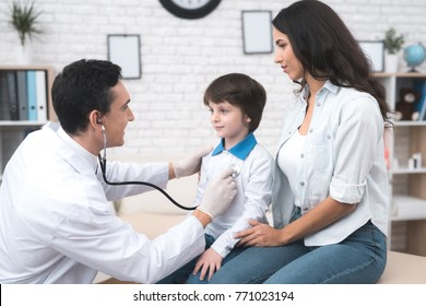 The doctor listens to the lungs of a sick boy in a stethoscope. He came with his mother to the doctor. The boy is ill with a cold. They are in the light office of the doctor.