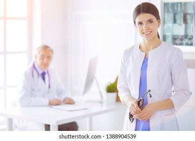 A doctor looking at the camera with her male colleage in the back of the conference room in hospital