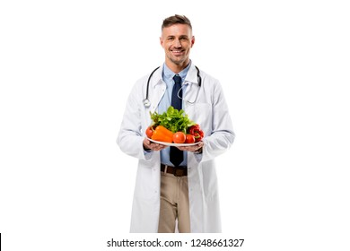 doctor looking at camera and holding plate of fresh vegetables isolated on white, healthy eating concept