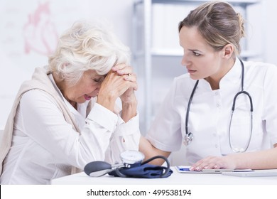 Doctor looking at the elder patient full of unease