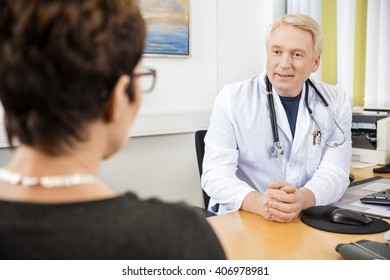 Doctor Looking At Female Patient At Desk