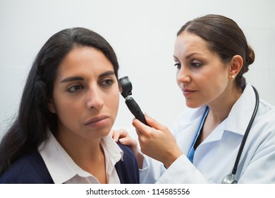 Doctor is looking into the ear of the woman with an instrument