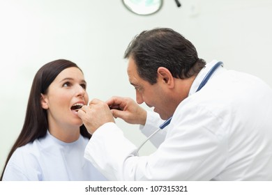 Doctor looking at the mouth of his patient in an examination room