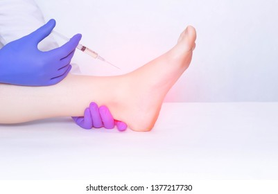 The doctor makes an injection into the ankle joint of the patient in plasma therapy to eliminate inflammation and pain, relieve edema, copy space