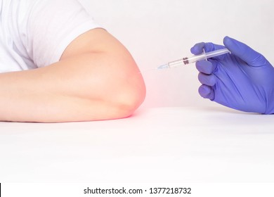 A doctor makes an injection into the elbow joint of a woman who has pain and inflammation in the elbow joint, a concept of modern medicine, plasma therapy injections and hilauric acid, copy space