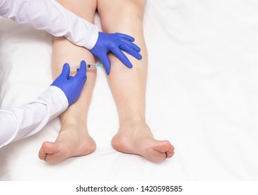 The doctor makes an injection of sclerotherapy to the patient who has varicose veins in the legs, miniphlebectomy, copy space