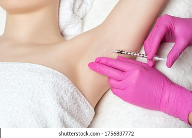 The doctor makes injections of botulinum toxin in the underarm area against hyperhidrosis. Women's cosmetology concept.