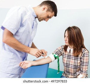 Doctor makes the patient an injection of a young woman.In the office of the doctor takes a blood sample to the test with the patient's arm