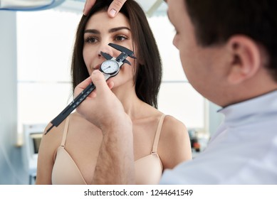 Doctor making anthropometry of female nose with calipers before surgery in beauty clinic