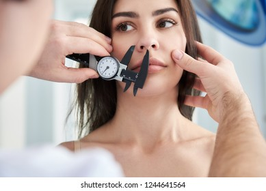 Doctor making anthropometry for pretty lady while using calipers before surgery