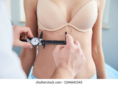 Doctor making anthropometry for woman before operation in beauty clinic