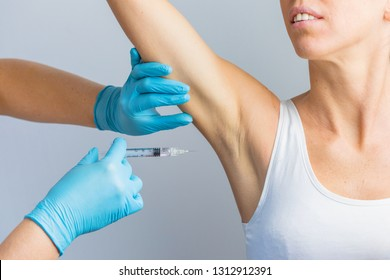 The doctor making intramuscular injection with syringe of botulinum toxin under arm against body sweat.