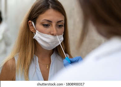 Doctor making a swab test to a young blonde woman for corona virus (covid-19) pandemic disease