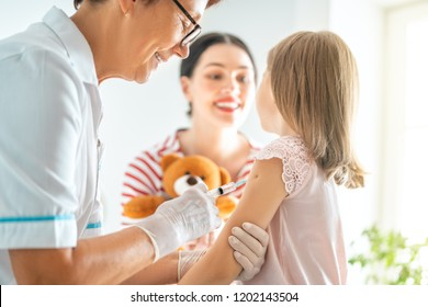 A doctor making a vaccination to a child. Kid with mother.