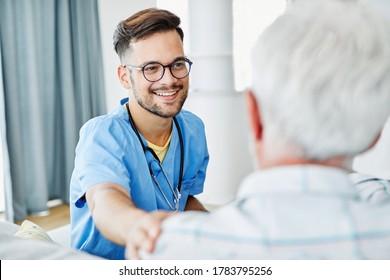 Ärztin oder männliche Pflegeperson, die zu Hause oder zu Hause einen Stock auf dem Sofa hält