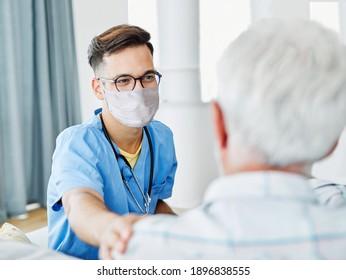 Ärztin oder männliche Pflegeperson mit Senioren, die zu Hause oder zu Hause eine Schutzmaske trägt