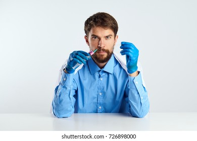doctor man holding a syringe sitting at a table on a light backgroun