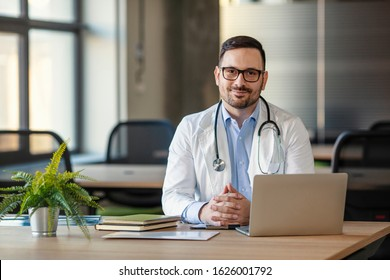 Doctor man sitting at the desk at his working place and smiling at camera. Perfect medical service in clinic. Portrait of a handsome young doctor. Happy doctor looking at camera