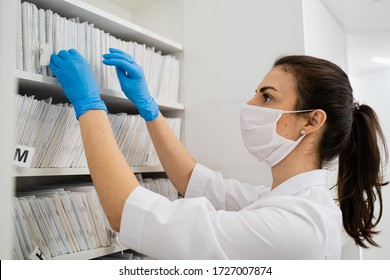 A doctor in a mask and white medical clothing is looking for medical documents in the archive in the new modern clinic