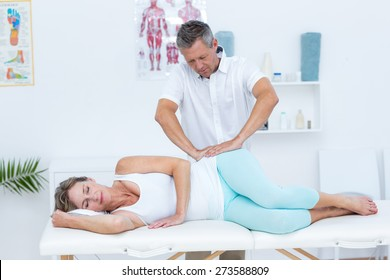 Doctor massaging his patient hip in medical office