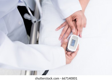 Doctor measure blood oxygen patient on the bed with oximeter.