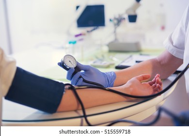 Doctor measures blood pressure of young girl, selective focus
