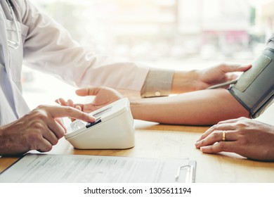 Doctor Measuring arterial blood pressure man patient on arm Health care in hospital