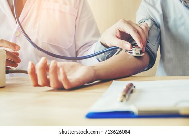 Doctor Measuring arterial blood pressure woman patient on right arm Health care in hospital